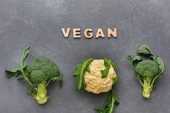 vegan Φρέσκα μπρόκολο και κουνουπίδι στο γκρίζο υπόβαθρο, τοπ άποψη Στοκ Εικόνα