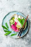 Vegan asian udon noodles soup bowl with ginger and mushrooms broth, tofu, snap peas, zucchini, watermelon radish and lime Royalty Free Stock Image