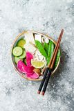 Vegan asian udon noodles soup bowl with ginger and mushrooms broth, tofu, snap peas, zucchini, watermelon radish and lime Royalty Free Stock Photo
