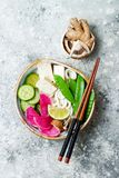 Vegan asian udon noodles soup bowl with ginger and mushrooms broth, tofu, snap peas, zucchini, watermelon radish and lime Stock Photography