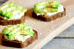 Vegan avocado and hummus sandwiches on a wooden board. Quick and healthy open sandwiches. Healthy eating. Meatless meal. Closeup Stock Photos
