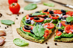 Vegan broccoli zucchini pizza crust with spinach pesto, tomatoes. Onion and olives. toning. selective focus Stock Photography
