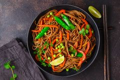 Vegan buckwheat soba noodles with vegetables in black plate on dark background, top view