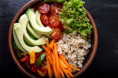 Vegan buddha bowl on black background. Top view. Bowl with carrot, lettuce, tomatoes cherry, pepper, avocado and porridge. Vegetar Royalty Free Stock Images