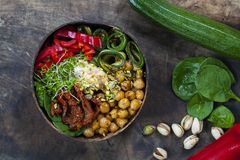 Vegan Buddha bowl with vegetables and chickpeas. Vegan Buddha bowl with courgettes, chickpeas, peppers and broccoli sprouts royalty free stock image