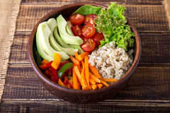 Vegan buddha bowl on wooden background. Top view. Bowl with carrot, lettuce, tomatoes cherry, pepper, avocado and porridge. Vegeta Stock Photos