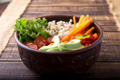Vegan buddha bowl on wooden background. Top view. Bowl with carrot, lettuce, tomatoes cherry, pepper, avocado and porridge. Vegeta Stock Image