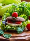 Vegan burger with lettuce, fresh cherry tomatoes and feta cheese. Burger: vegan burger with lettuce, fresh cherry tomatoes and feta cheese on wooden background Royalty Free Stock Photos