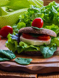 Vegan burger with lettuce, fresh cherry tomatoes and feta cheese. Burger: vegan burger with lettuce, fresh cherry tomatoes and feta cheese on wooden background Royalty Free Stock Images