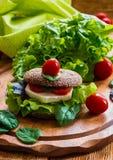 Vegan burger with lettuce, fresh cherry tomatoes and feta cheese. Burger: vegan burger with lettuce, fresh cherry tomatoes and feta cheese on wooden background Royalty Free Stock Image