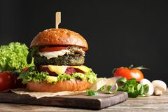 Vegan burger and vegetables on table against dark background. royalty free stock image