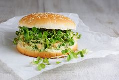 Vegan burger. A vegetarian burger made from a gluten-free bun with chickpeas, avocado and herbs, radish sprouts. A quick and healthy lunch idea that you feel Royalty Free Stock Photo
