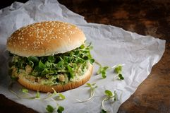 Vegan burger. A vegetarian burger made from a gluten-free bun with chickpeas, avocado and herbs, radish sprouts. A quick and healthy lunch idea that you feel Stock Photos