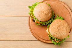 Vegan burgers with fresh vegetables on rustic wooden table, top view. Healthy fast food background with copy space royalty free stock images