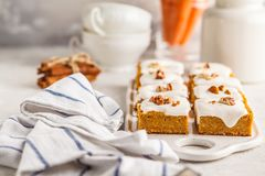 Vegan carrot cake with coconut cream and pecan, plant based diet. Vegan carrot cake with coconut cream and pecans on white board. Clean eating, healthy food royalty free stock images