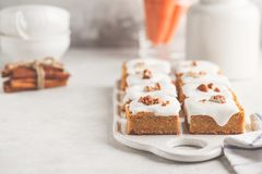 Vegan carrot cake with coconut cream and pecan, plant based diet. Vegan carrot cake with coconut cream and pecans on white board. Clean eating, healthy food stock images