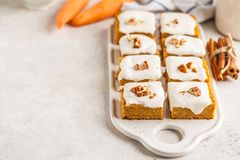 Vegan carrot cake with coconut cream and pecan, plant based diet. Vegan carrot cake with coconut cream and pecans on white board. Clean eating, healthy food royalty free stock photography