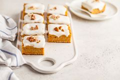 Vegan carrot cake with coconut cream and pecan, plant based diet. Vegan carrot cake with coconut cream and pecans on white board. Clean eating, healthy food stock photos