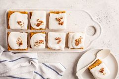 Vegan carrot cake with coconut cream and pecan, plant based diet. Vegan carrot cake with coconut cream and pecans on white board. Clean eating, healthy food royalty free stock photo