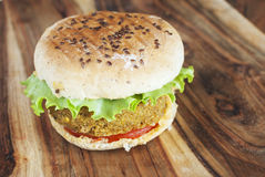 Vegan chickpea burger on a wooden table. Concept of a healthy vegetarian fast food. Selective focus Royalty Free Stock Image