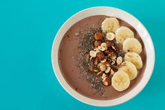 Vegan chocolate banana protein smoothie bowl. Chocolate hazelnut smoothie bowl topped with sliced banana, chia seeds, chopped chocolate, nuts and sesame seeds royalty free stock photography