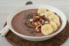 Vegan chocolate banana protein smoothie bowl. Chocolate hazelnut smoothie bowl topped with sliced banana, chia seeds, chopped chocolate, nuts and sesame seeds stock photography