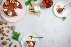 Vegan chocolate cake, strawberries, walnuts, cocoa and other dessert ingredients. Flatlay with vegan chocolate cake, strawberries, walnuts, cocoa and other royalty free stock image