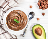 Vegan chocolate pudding from avocado and hazel milk. Vegan raw chocolate pudding from avocado, cocoa and hazel milk decorated with mint leaves and crushed nut on royalty free stock images