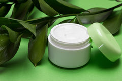 Vegan cosmetics with components of plant origin. Open jar of moisturizing cream and green leaves. Vegan cosmetics with components of plant origin stock images