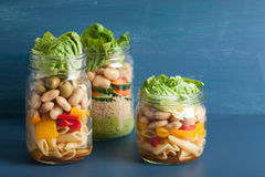 Vegan couscous and pasta salad in mason jars with vegetables bea Stock Images