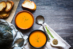 Vegan Creamy Delicious  Pumkin Soup. With fresh vegaetables and sliced of bread over a wooden background Stock Image