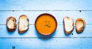 Vegan Creamy Delicious  Pumkin Soup. With fresh vegaetables and sliced of bread over a wooden background Royalty Free Stock Photo