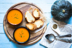 Vegan Creamy Delicious  Pumkin Soup. With fresh vegaetables and sliced of bread over a wooden background Stock Photo