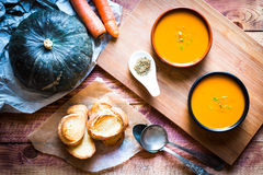 Vegan Creamy Delicious Pumkin Soup. With fresh vegaetables and sliced of bread over a wooden background royalty free stock photos
