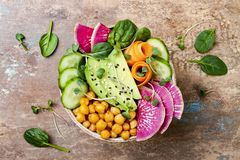 Vegan, detox Buddha bowl recipe with avocado, carrots, spinach, chickpeas and radishes. Top view, flat lay, copy space. Vegan, detox Buddha bowl recipe with Stock Images