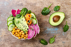 Vegan, detox Buddha bowl recipe with avocado, carrots, spinach, chickpeas and radishes. Top view, flat lay, copy space. Vegan, detox Buddha bowl recipe with Royalty Free Stock Photo
