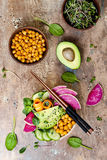 Vegan, detox Buddha bowl recipe with avocado, carrots, spinach, chickpeas and radishes. Top view, flat lay, copy space. Vegan, detox Buddha bowl recipe with Stock Photo