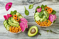 Vegan, detox Buddha bowl recipe with avocado, carrots, spinach, chickpeas and radishes. Top view, flat lay, copy space. Vegan, detox Buddha bowl recipe with Stock Photography
