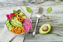 Vegan, detox Buddha bowl recipe with avocado, carrots, spinach, chickpeas and radishes. Top view, flat lay, copy space. Royalty Free Stock Photos