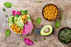 Vegan, detox Buddha bowl recipe with avocado, carrots, spinach, chickpeas and radishes. Top view, flat lay, copy space. Vegan, detox Buddha bowl recipe with Stock Image