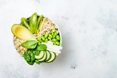 Vegan, detox green Buddha bowl recipe with quinoa, avocado, cucumber, spinach, tomatoes, mung bean sprouts, edamame beans, daikon Stock Photo