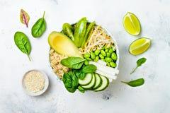 Vegan, detox green Buddha bowl recipe with quinoa, avocado, cucumber, spinach, tomatoes, mung bean sprouts, edamame beans, daikon Royalty Free Stock Images