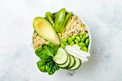 Vegan, detox green Buddha bowl recipe with quinoa, avocado, cucumber, spinach, tomatoes, mung bean sprouts, edamame beans, daikon Royalty Free Stock Photography