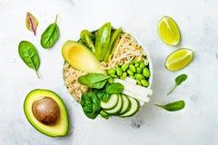 Vegan, detox green Buddha bowl recipe with quinoa, avocado, cucumber, spinach, tomatoes, mung bean sprouts, edamame beans, daikon Stock Photography
