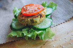 Vegan diet Burger appetizer with chickpeas lentil cutlet, cucumber, fresh lettuce, and tomato. Sprinkle with sesame Stock Images