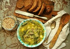 Vegan dish: quinoa soup with organic cabbage and potatoes. Vegan food : quinoa soup with organic cabbage and potatoes with whole wheat bread on a vintage table Royalty Free Stock Image