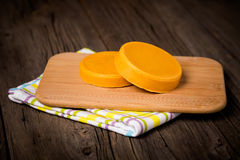 Vegan diy homemade yellow cheese. Homemade DIY natural vegan healthy yellow cheese made of potatoes, carrot and nutritional yeast a wooden table Stock Images