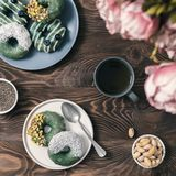 Vegan donuts topped spirulina glaze. Vegan doughnuts with chia seeds topped with healthy spirulina glaze with pistachio,desiccated coconut and blueberry.Blue royalty free stock image