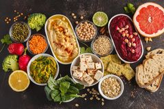 Vegan food background. Vegetarian snacks: hummus, beetroot hummus, green peas dip, vegetables, cereals, tofu. Top view, dark back. Vegan food background stock image
