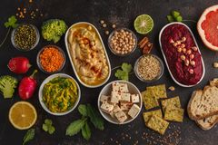 Vegan food background. Vegetarian snacks: hummus, beetroot hummus, green peas dip, vegetables, cereals, tofu. Top view, dark back. Vegan food background stock images